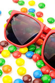 Red sunglasses on chocolate color coated candies  — Stock Photo