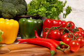Pepper and tomatoes on a wooden surface — Stock Photo