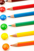 Different color pencils and same color candies — Stock Photo