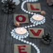 Pearl beads around three candles and letters L O V E — Stock Photo