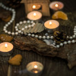Tea candles and pearl beads on a rustic surface — Stock Photo #42200117