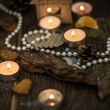 Tea candles and pearl beads on a rustic surface — Stock Photo