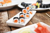 Salmon maki sushi on a white plate — Stock Photo