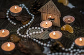 Tea candles and pearls with a cardboard house — Stock Photo