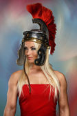 Gladiatrix in a shiny helmet with red feathers — Stock Photo