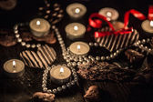 Dark romantic photo of tea candles and pearls — Stock Photo