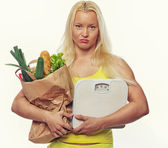 Woman with food and scales — Stock Photo