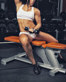 Woman in gym with dumbbell — Stock Photo