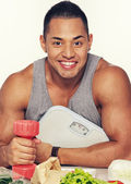 Man with food and dumbbells — Stockfoto