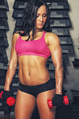 Brunette woman with dumbbells — Stock Photo