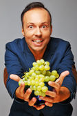Man with grapes — Stockfoto