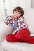 Boy on white sofa — Stock Photo