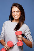 Young girl holding two plastic dumbbells — Stock Photo