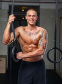 Smiling tattooed athlete posing in a gym — Foto Stock