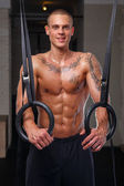 Muscled tattoed man excercising with rings — Stock Photo