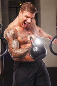 Tattooed athlete lifting weights — Stock Photo