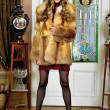 Stock Photo: Beautiful woman in fur coat in the luxurious antique interior.