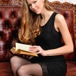 Beautiful woman with book sitting on the sofa in antique interio — Stock Photo #12429882