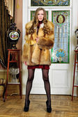 Beautiful woman in fur coat in the luxurious antique interior. — Stock Photo