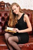 Schöne frau mit buch, sitzt auf dem sofa in antik interio — Stockfoto