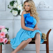 Beautiful blonde woman in blue dress in luxury interior. - Stockfoto