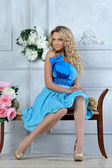 Beautiful blonde woman in blue dress in luxury interior. — Stock Photo