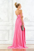 Beautiful blonde woman in a pink evening long dress. — Stok fotoğraf