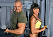 Man and woman are doing exercises in a sport club. — Stock Photo