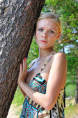 Beautiful blonde woman standing at the tree — Stock Photo