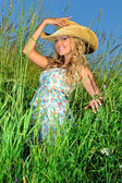Beautiful blonde woman in straw hat on the nature. — Stock Photo