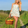 Stock Photo: Rural landscape with beautiful blonde walking at the meadow.