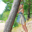 Beautiful blonde woman standing at the tree — Stockfoto