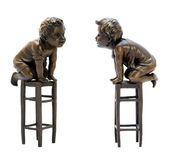 Estatuilla de bronce antigua que representa a un niño sentado en un taburete. — Foto de Stock