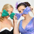 Two beautiful woman in evening gowns having fun. - Stock Photo
