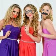 Stock Photo: Three women in evening gown with masks.