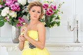 Beautiful woman in yellow dress in luxury studio. — Stock Photo