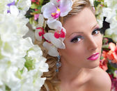 Beautiful chic woman around the flowers. — Stock Photo