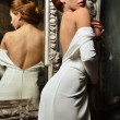 Stock Photo: Beautiful woman in white dress with naked back.