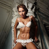 Beautiful woman in white underwear in palace — Stock Photo