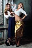 Two beautiful women posing in obsolete interior. — Stock Photo