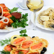 Table with food of meat, salmon rolls, dumplings and white wine. — Stock Photo #42791749