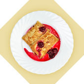 Dish of crepes with cherry sause on white plate. — Stock Photo