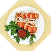 Dish of meat on skewer with tomato sause on white plate. — Stock Photo