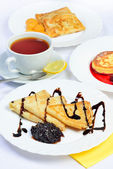 Food of Crepes, cheesecakes with berry sause and cup of tee. — Stock Photo