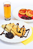 Food of crepes, cheesecakes with berry sause and glass of juice. — Stock Photo