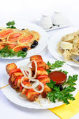 White table with food of meat, salmon rolls and dumplings. — Stock Photo