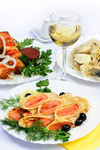 Table with food of meat, salmon rolls, dumplings and white wine. — Stock Photo