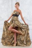 Schöne bonde frau im leoparden gemusterte langes kleid. — Stockfoto