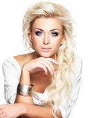 Linda mulher loira com longo encaracolado cabelo e estilo de maquiagem. — Fotografia Stock