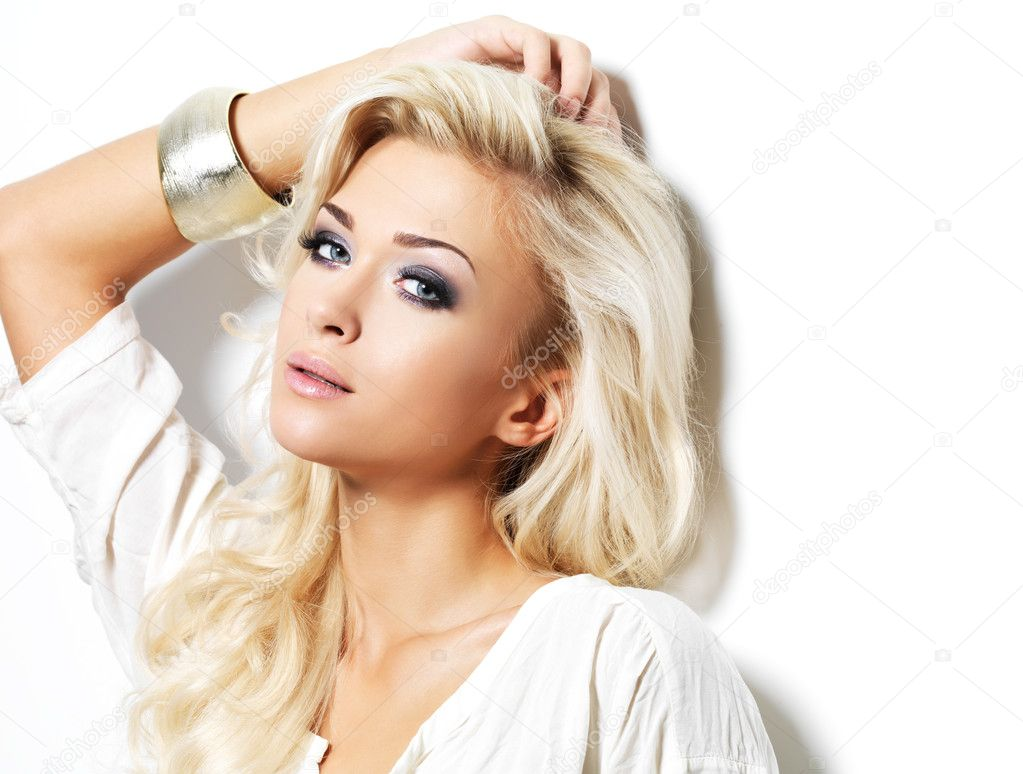 Beautiful blond woman with long curly hair and style makeup. Girl posing on white background — Stock Photo #14516585